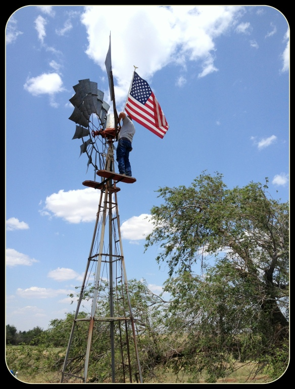 Cattleman hanging the flag in SW Oklahoma on 4th of July